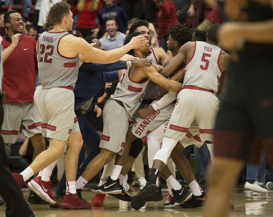 Stanford players mob Daejon Davis, second from right, after his 3-point buzzer beater gave his team the win over Southern California in an NCAA college basketball game, Sunday, Jan. 7, 2018, in Stanford, Calif. Stanford won 77-76. (AP Photo/D. Ross Cameron) Photo: D. Ross Cameron, Associated Press