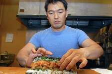 "Brad Horrigan | New Haven Register.  BH0519. New Haven, Connecticut - 02.04.10:  Bun Lai makes a ""catfish blues"" roll for the photograph.  The roll is made with sustainably-raised domestic catfish, brown rice, quinoa, apricot and chives and various seeds and seasonings."