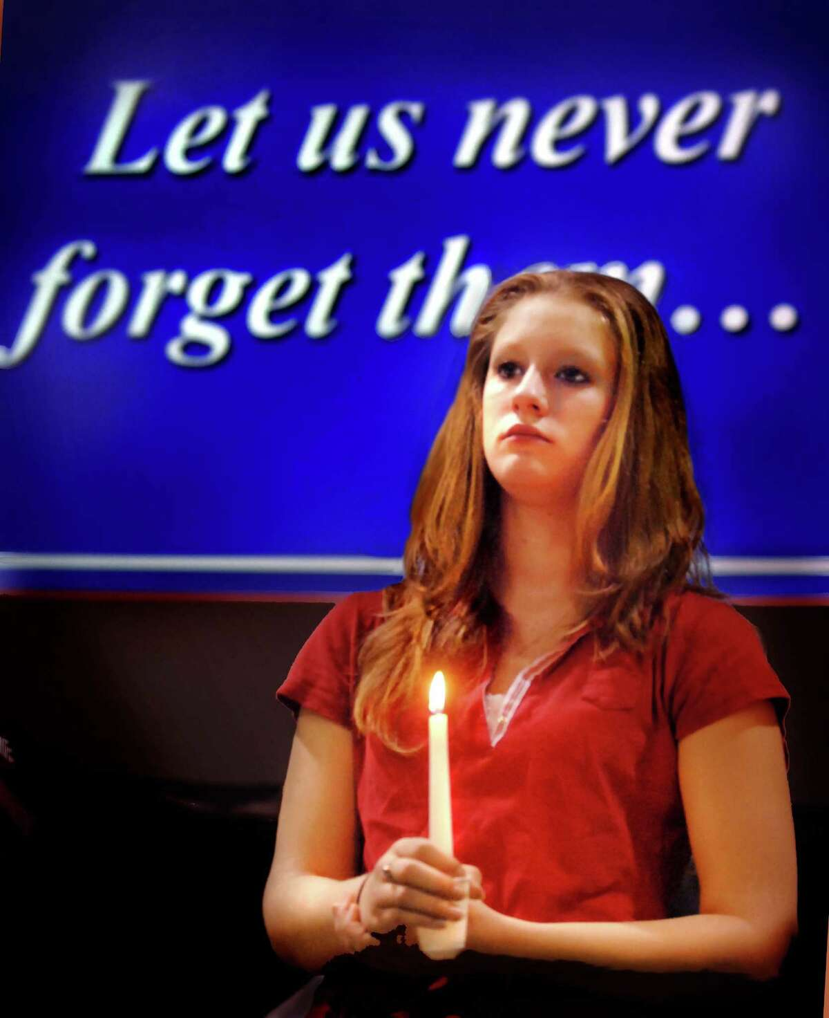 (ms091107)O/Brian---Senior, Jean-Marie Wardle holds a candle during ceremonies at Emmett O'Brien Technical High School in Ansonia marking the anniversary of the 9/11 attacks. Members of the Honor Society held candles during a slide presentation. Melanie Stengel/Register
