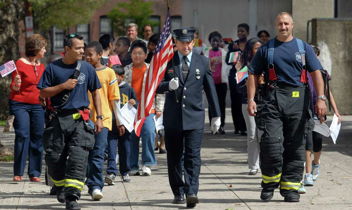 NE9/11/08 1ERNineEleven ML0478F New Haven Engine 8 Firefighters left to right Armando Hernandez, Ray Saracco and Michael Guercia lead a group of East Rock Magnet School (New Haven) ESOL students down Nash St. to lay flowers at a piece of a beam from the World Trade Center that is now a memorial on Edwards St. Photo by Mara Lavitt