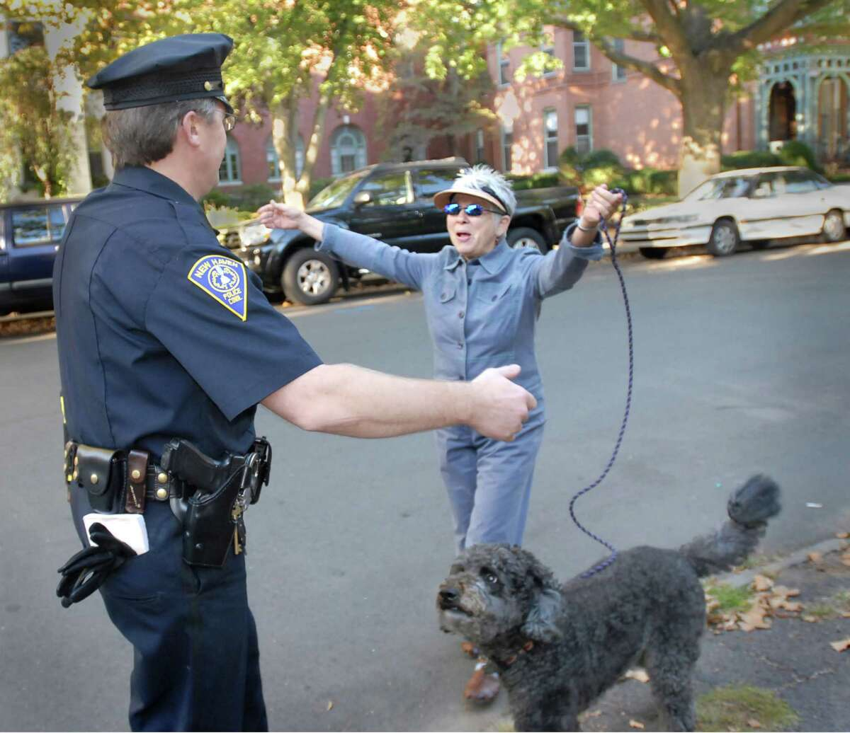 (MS092107)-Jane Lederer, who lives in the Wooster Square neighborhood, welcomes New Haven police officer, Peter Krause, back to his beat. With Lederer is her poodle, Rosy. Melanie Stengel/Register