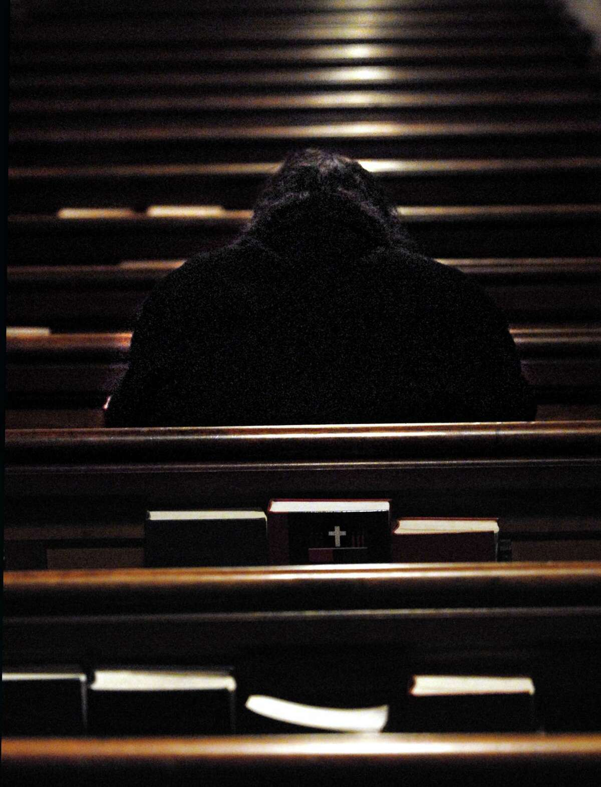Brad Horrigan | New Haven Register. BH0250. New Haven, Connecticut - 12.18.08: A visitor sits in the Episcopal Church of St. Paul and St. James during a Blue Christmas celebration Thursday night. The second annual prayer service is designed to attract those who have suffered losses of family or friends and may not be looking forward to Christmas.