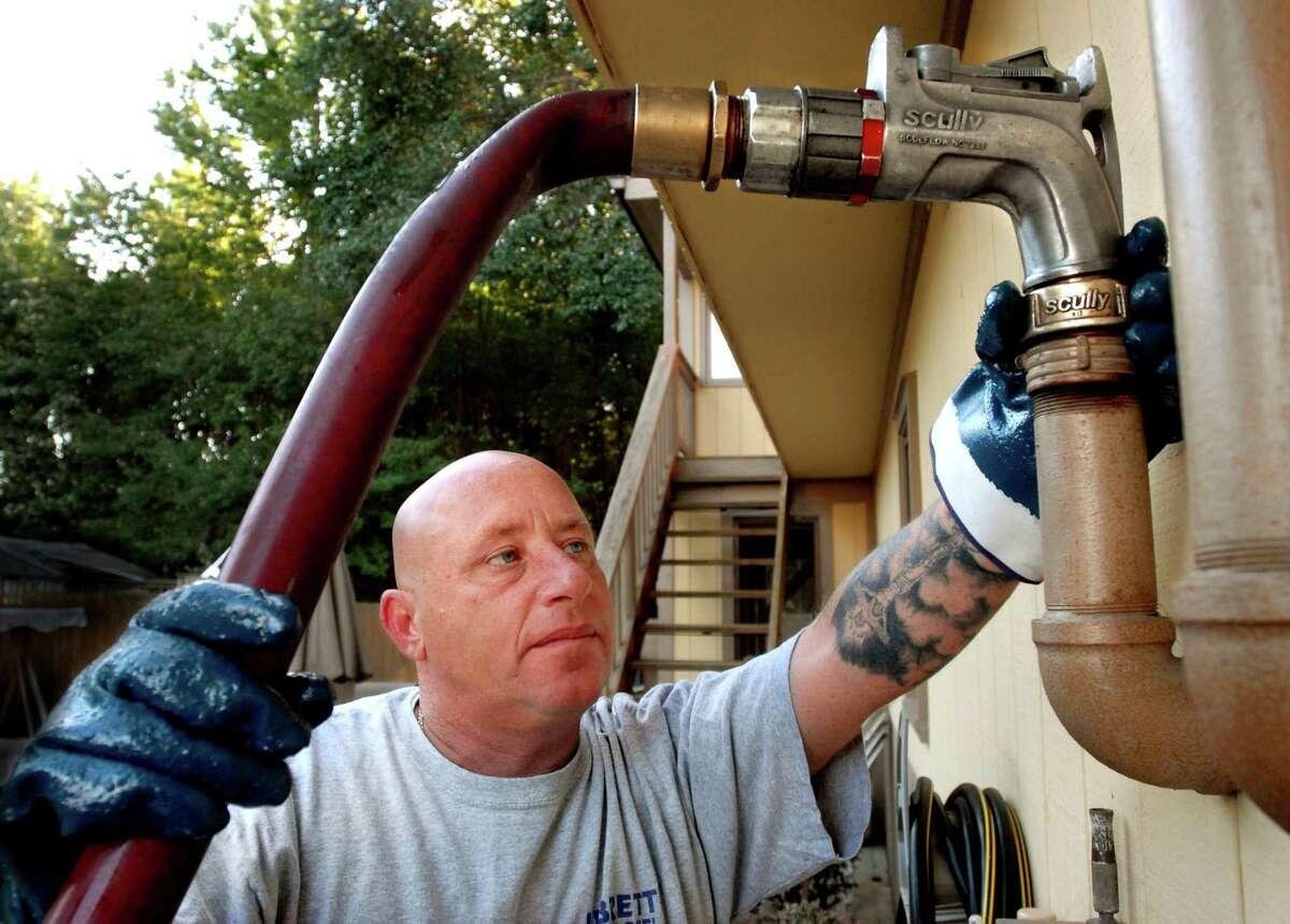 (ms093009)-Nick Libretti fills an oil tank in East Haven. Melanie Stengel/Register