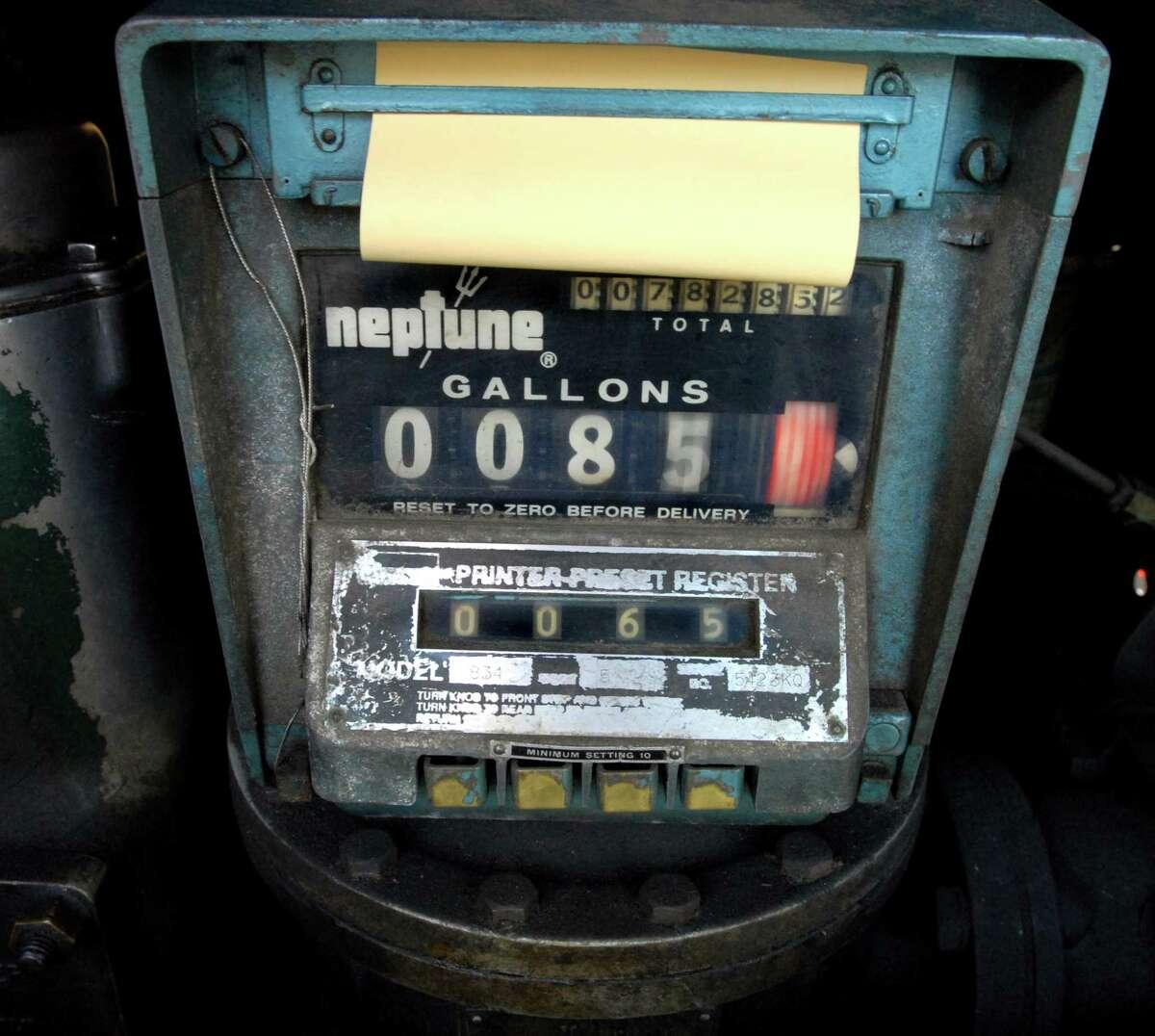 (ms093009)-The meter registers gallons as Nick Libretti fills an oil tank in East Haven. Melanie Stengel/Register