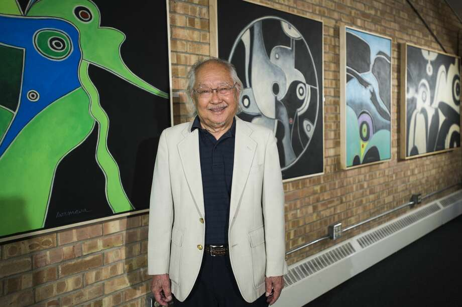 "Local artist Robert Iwamasa poses for a portrait next to his paintings inside his new exhibit, called ""A Wonderful Line,"" currently on display at Creative 360 in Midland. (Katy Kildee/kkildee@mdn.net) Photo: (Katy Kildee/kkildee@mdn.net)"