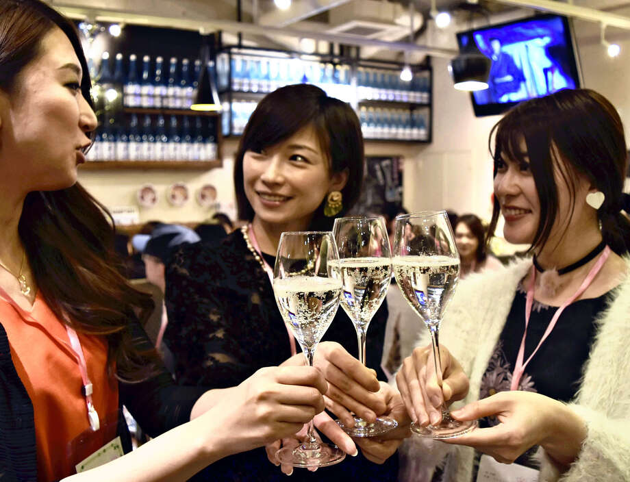 Nihonshu joshikai group leader Aimee Ujiie, right, raises a glass of sparkling sake with attendees of a sake-themed event in Tokyo. Photo: Japan News-Yomiuri Photo / Japan News-Yomiuri