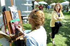 mi-art show-ag-5/10/09 Emily Niedzwiecki (right) of Massachusetts walks by Lori Neumann (left) of Salem, Connecticut, painting a sheep at the Meet the Artists and Artisans show on the Milford Green on 5/10/2009. Photo by Arnold Gold   AG0310E