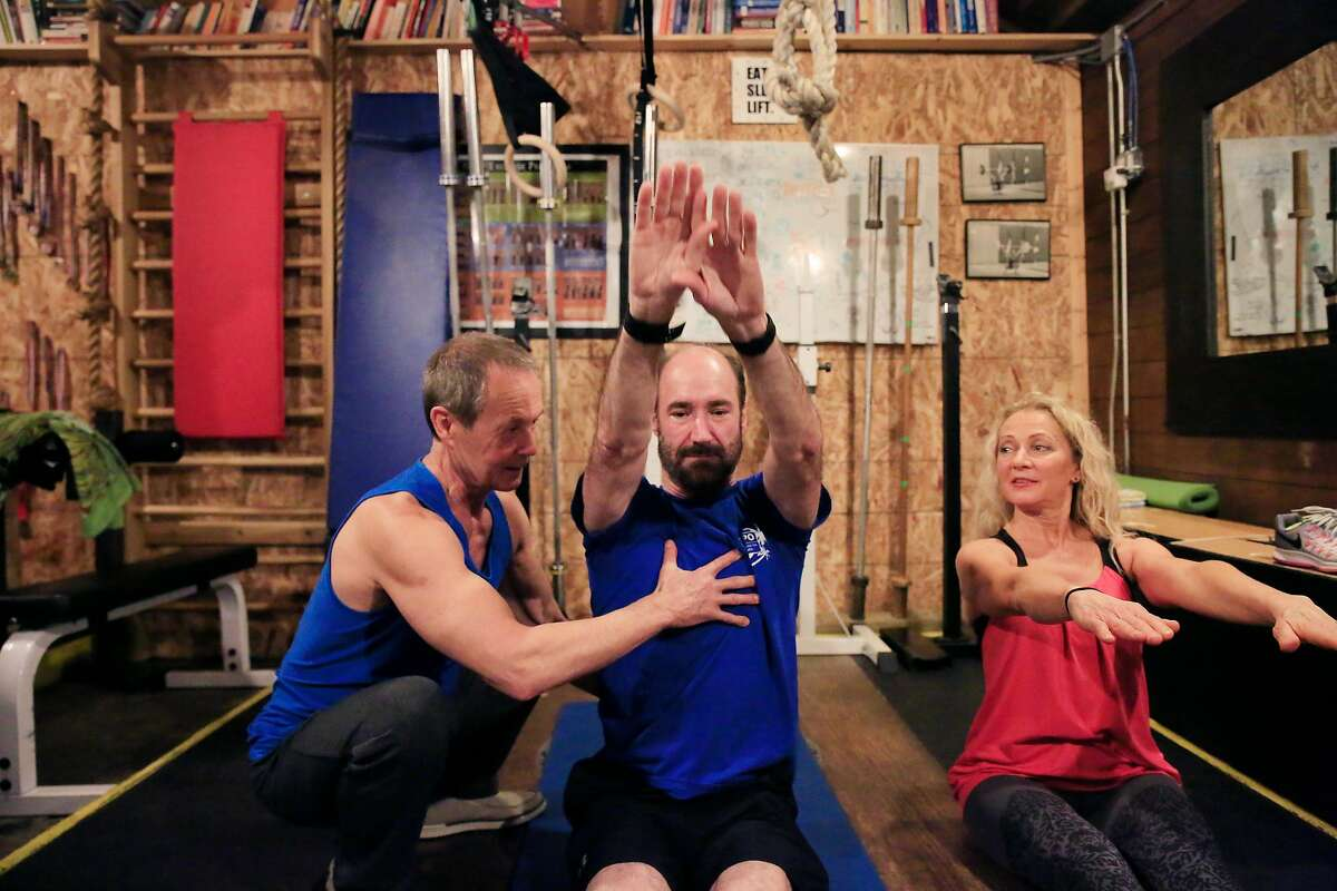 Jerzy Gregorek (right) and Aniela Gregorek (left) work with Michael Snyder (center), head of genomics research at Stanford, during a mini workout in the gym at their home on Tuesday, January 2, 2018 in Woodside, Calif.