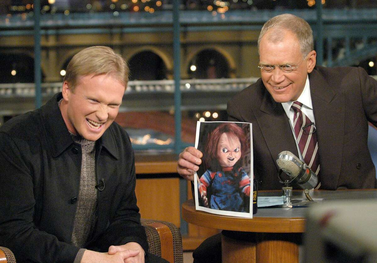 """Tampa Bay Buccaneers coach Jon Gruden, left, who is also known as """"Coach Chucky"""" for his quirky resemblance to the horror movie doll, shares a laugh with host David Letterman who holds a photo of the doll during the taping of CBS' """"Late Show with David Letterman,"""" Tuesday, Feb 4, 2003, in New York."""