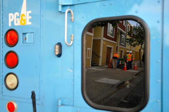 PG&E Workers are reflected in the window of one of their trucks as they inspect the scene where one of their co-workers was injured due to an electric arc accident in the Bayview area of San Francisco on Sunday, May 05, 2013.