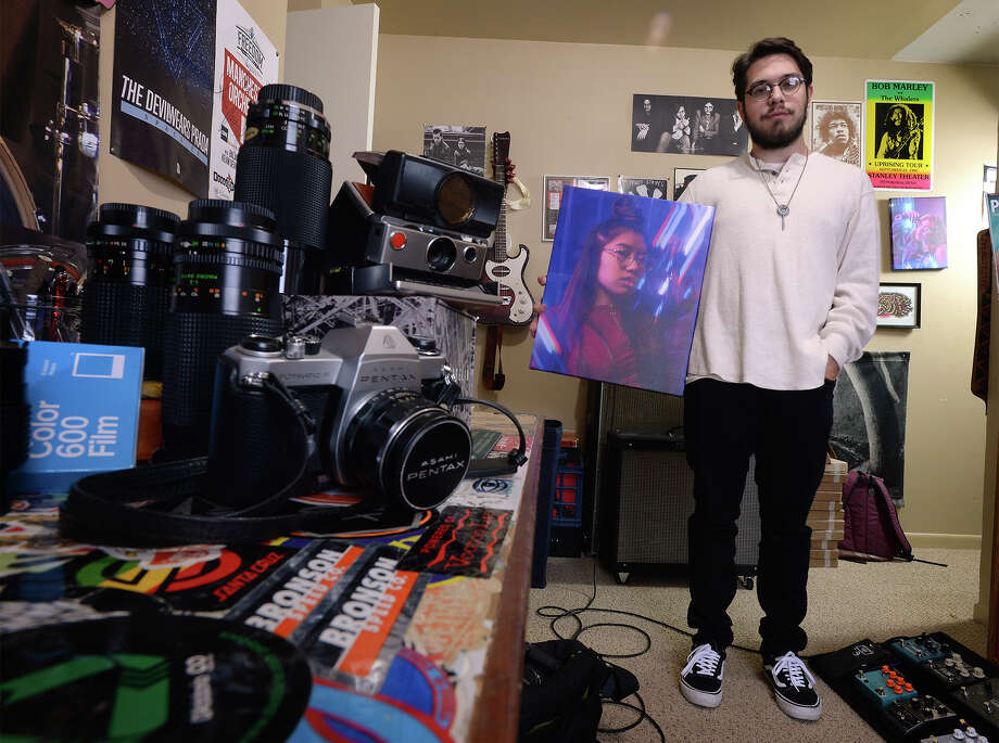Dylan Newton holds one of his photos at his home. Newton uses prisms and neon signs to add color and flare to his images. Photo taken Tuesday, January 02, 2018 Guiseppe Barranco/The Enterprise Photo: Guiseppe Barranco, Photo Editor / Guiseppe Barranco ©