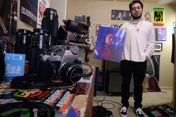 Dylan Newton holds one of his photos at his home. Newton uses prisms and neon signs to add color and flare to his images. Photo taken Tuesday, January 02, 2018 Guiseppe Barranco/The Enterprise