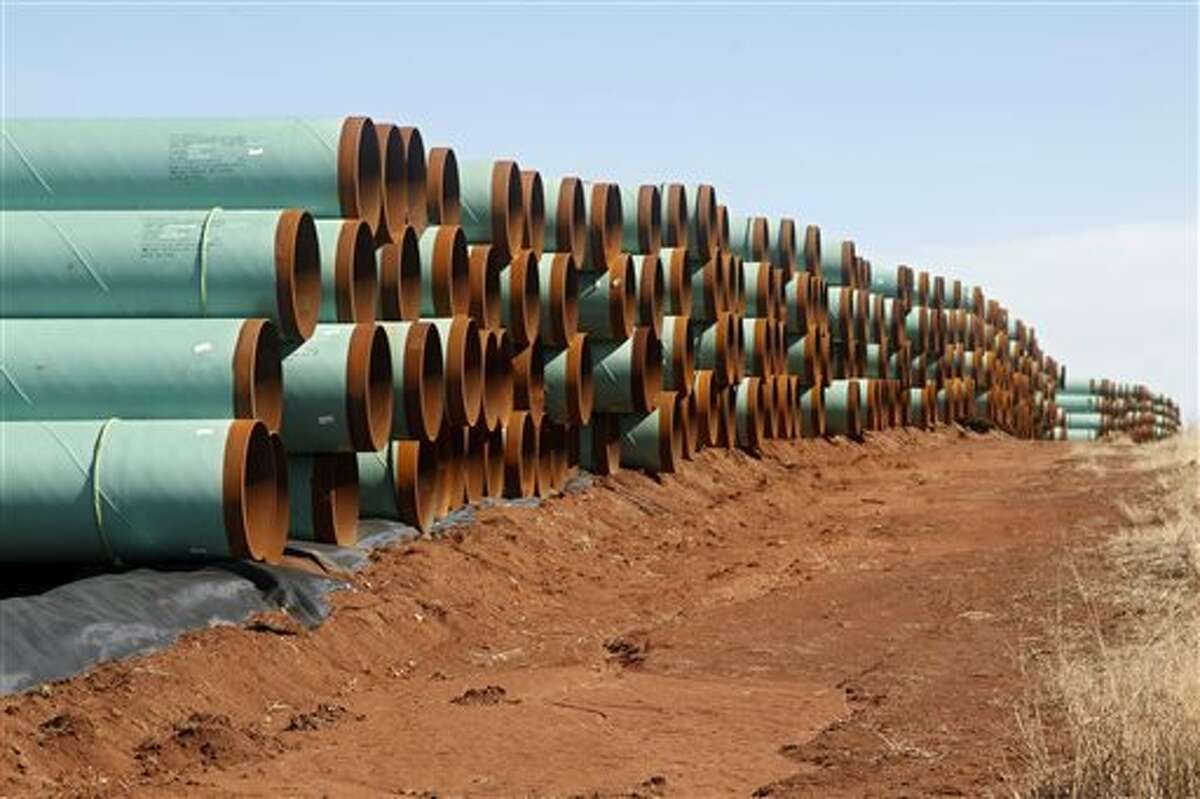 FILE - In this Feb. 1, 2012 file photo, miles of pipe for the stalled Canada-to-Texas Keystone XL pipeline are stacked in a field near Ripley, Okla.
