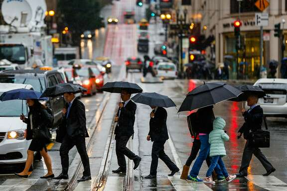 People cross Geary Street during a rainstorm in San Francisco, Calif., on Monday, Jan. 8, 2018.