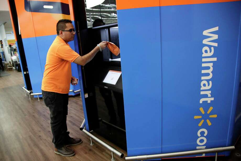 In this Thursday, Nov. 9, 2017, photo, Setal Gandhi, a department manager at a Walmart store in Secaucus, N.J., demonstrates how shoppers can pick up online orders at a tower near the entrance of the store. (AP Photo/Julio Cortez) Photo: Julio Cortez / Copyright 2017 The Associated Press. All rights reserved.