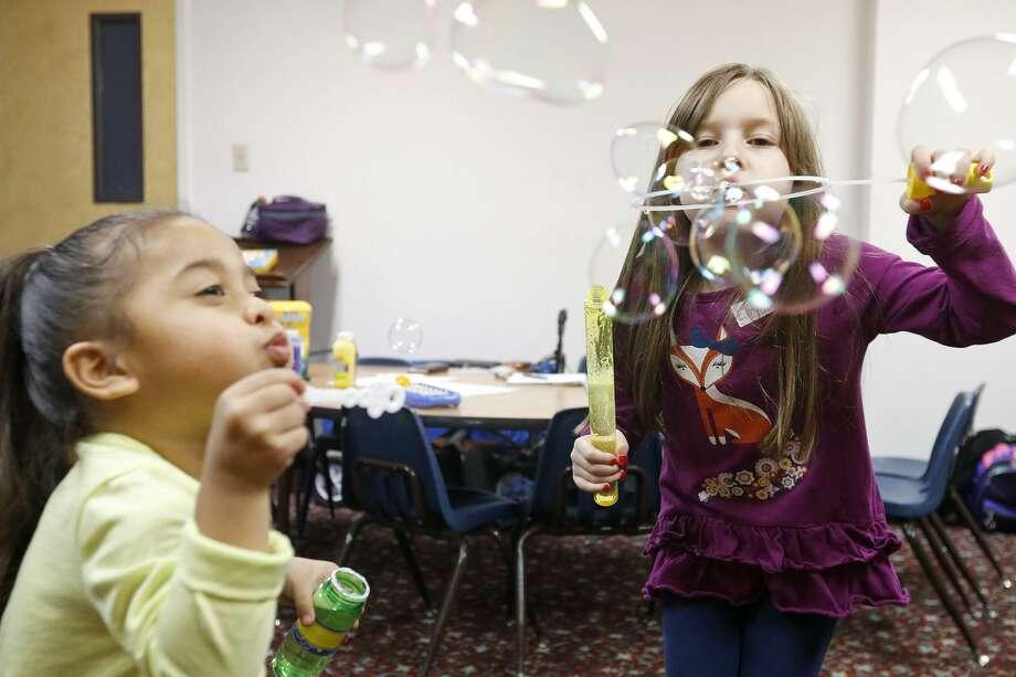 Ann Marie Becerra, 3, (left) and Emma Summers, 7, blow bubbles Monday while staying at the Lil' Roadrunners Children's Evening program. Photo: Edward A. Ornelas / San Antonio Express-News / © 2018 San Antonio Express-News