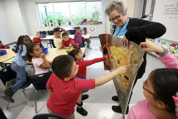 "Art teacher Carolyn Jackson showcases a picture of Gustav Klimt's ""The Kiss"" painting to a kindergarten class at Robinson Elementary on Monday. About 550 students returned to their home campus after it was flooded during Hurricane Harvey."