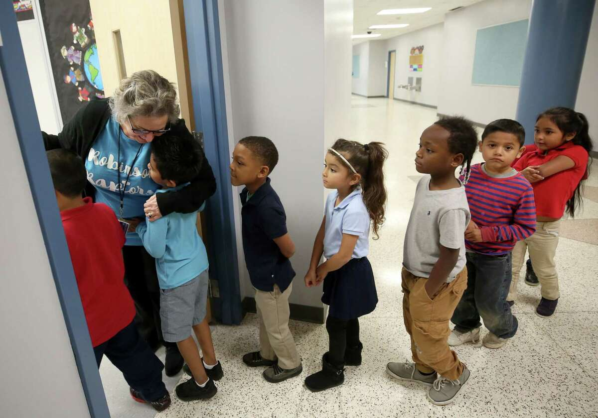 Carolyn Jackson, left, welcomes Doris Irizarry's kindergarten students into her art classroom at Robinson Elementary - the first of seven flood-damaged HISD schools to reopen since Harvey.
