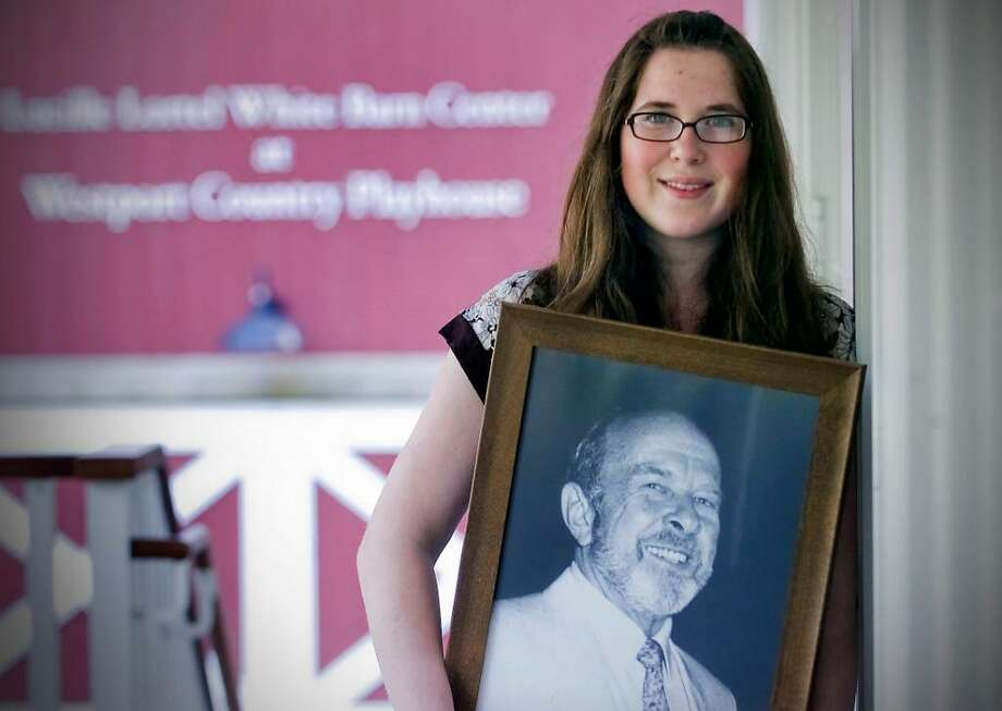 Westport Country Playhouse intern Gwendolyn McKenzie with portrait of her grandfather, James B. McKenzie, who served as executive producer for many of his 41 seasons (1959-1999) at Westport Country Playhouse. Photo: Contributed Photo, Kathleen O'Rourke / Fairfield Citizen