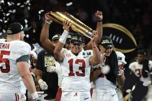 Alabama quarterback Tua Tagovailoa (13), who replaced starter Jalen Hurts after a scoreless first half for the Crimson Tide, hoists the national championship trophy Monday night.