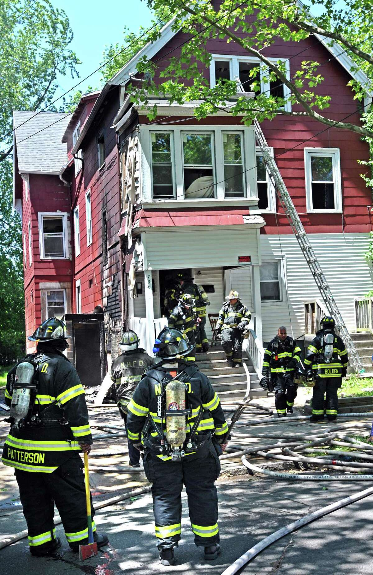 New Haven-- Firefighters clean up after battling a blaze along Orchard Street near Charles Street. . Photo-Peter Casolino/New Haven Register Cas060311 6/3/11