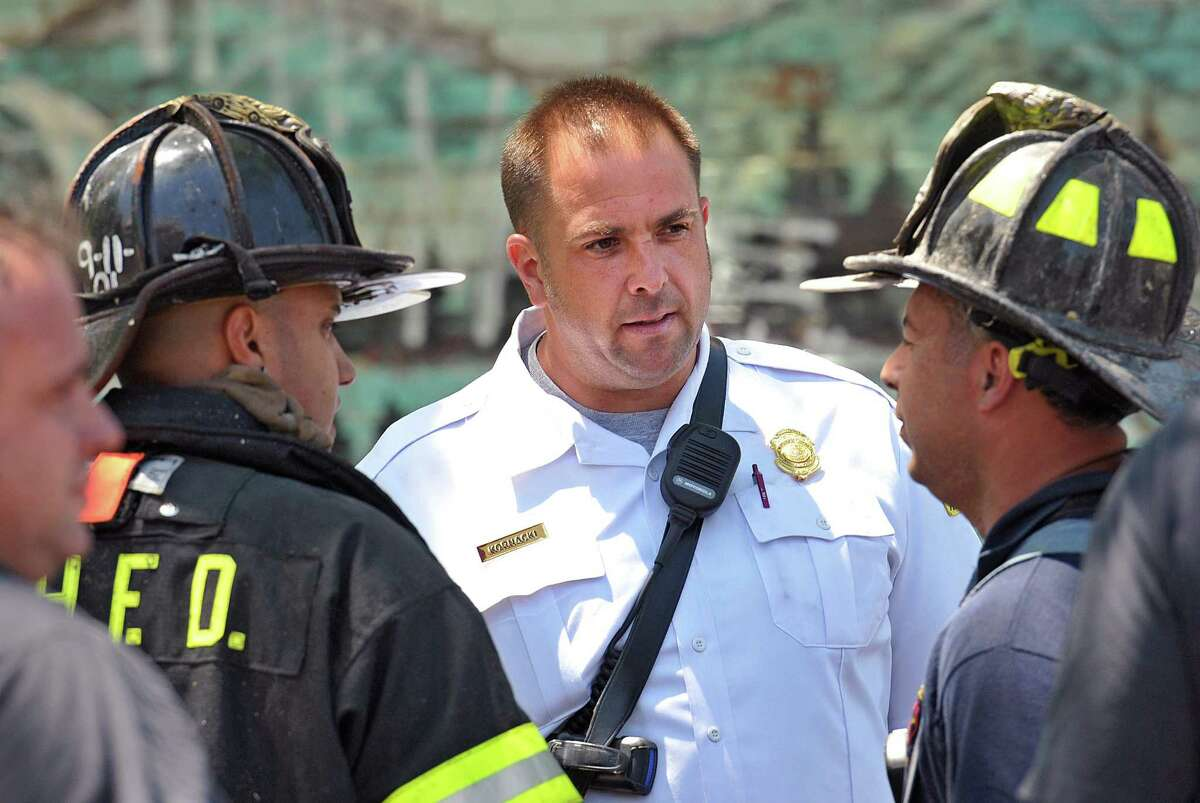 New Haven-- New Haven Fire Inspector Todd Kornacki talks with other firefighters at the scene of a fire at Orchard Street near Charles Street. Kornacki, who was in the area at the time of the call, helped evacuate the home along with a New Haven Police Officer before the trucks arrived. Photo-Peter Casolino/New Haven Register Cas060311 6/3/11