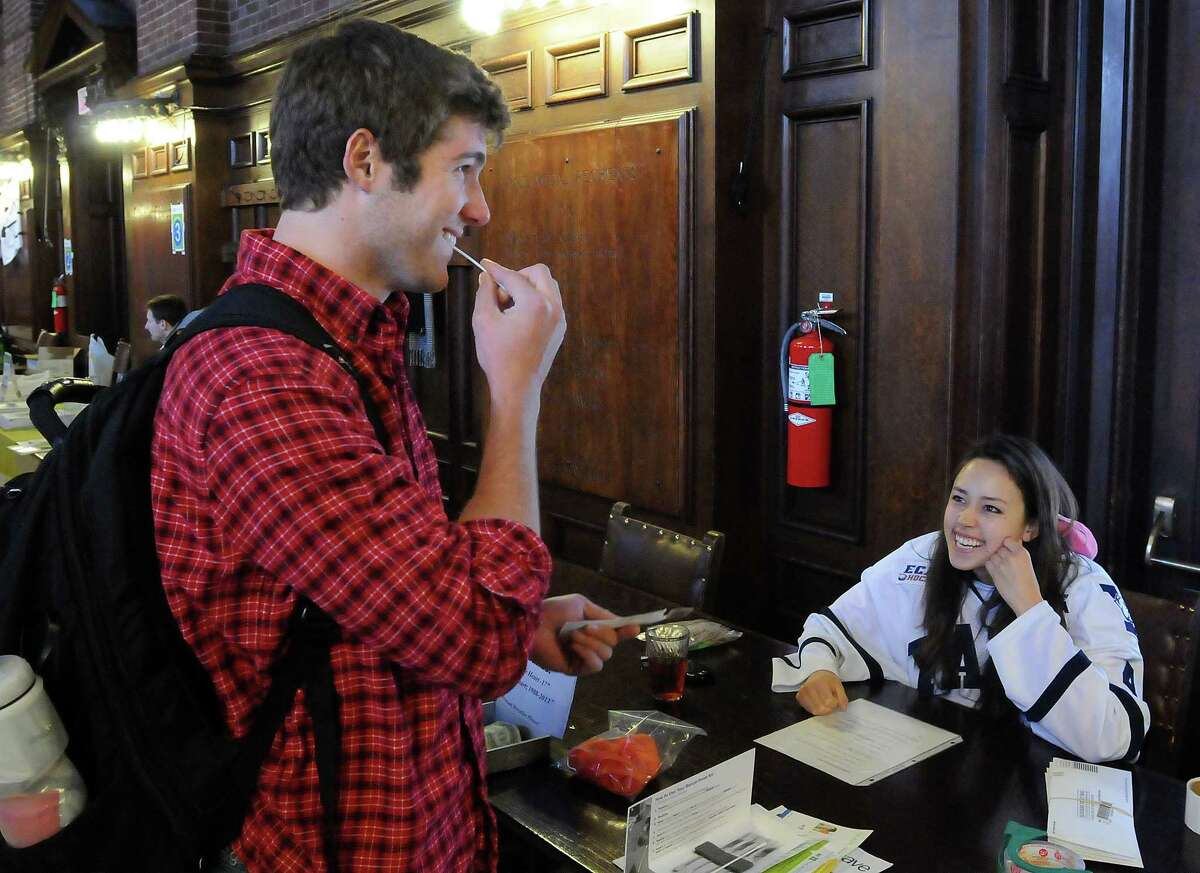 Yale Commons: a bone marrow drive was run in memory of Mandi Schwartz, a Yale hockey player who died recently from cancer. Freshman and track team member Dana Lindberg left does one of four cheek swabs under the oversight of Yale hockey player Tara Tomimoto. Photo by Mara Lavitt/New Haven Register 4/21/11