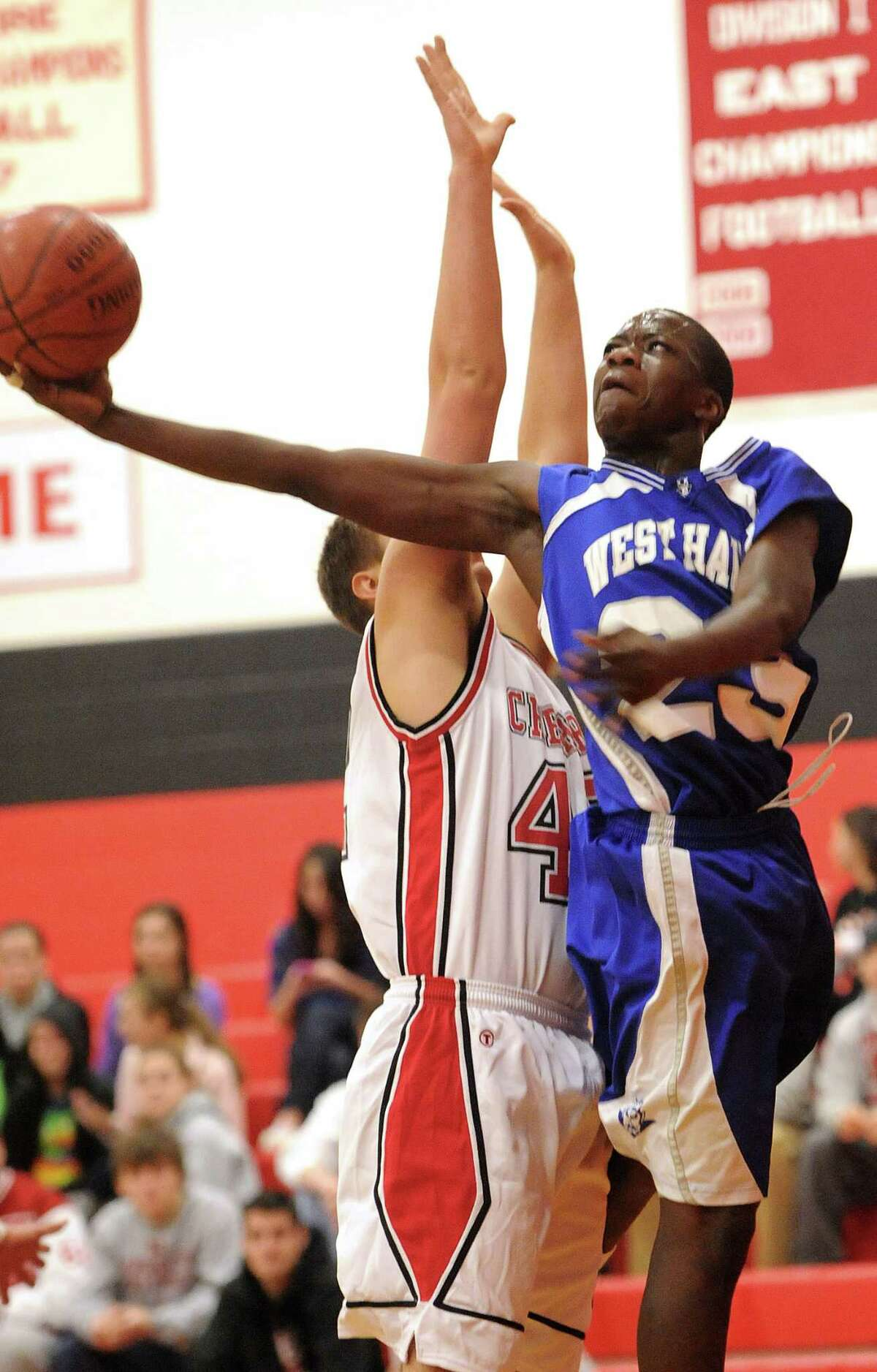 Cheshire--West Haven's Kadialy Toure gets the shot off as Cheshire's Gil Lassen defends. Photo by Brad Horrigan/New Haven Register-12.30.10.