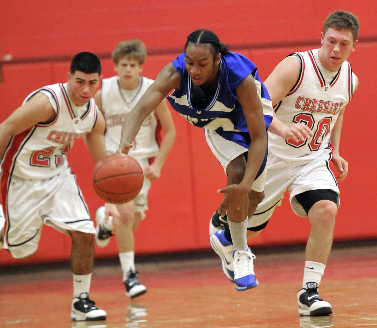 Cheshire--West Haven's Tieron Jackson, center, beats Cheshire's Matt Bailey, left, and Billy Weyrauch to a lose ball Thursday night. Photo by Brad Horrigan/New Haven Register-12.30.10.