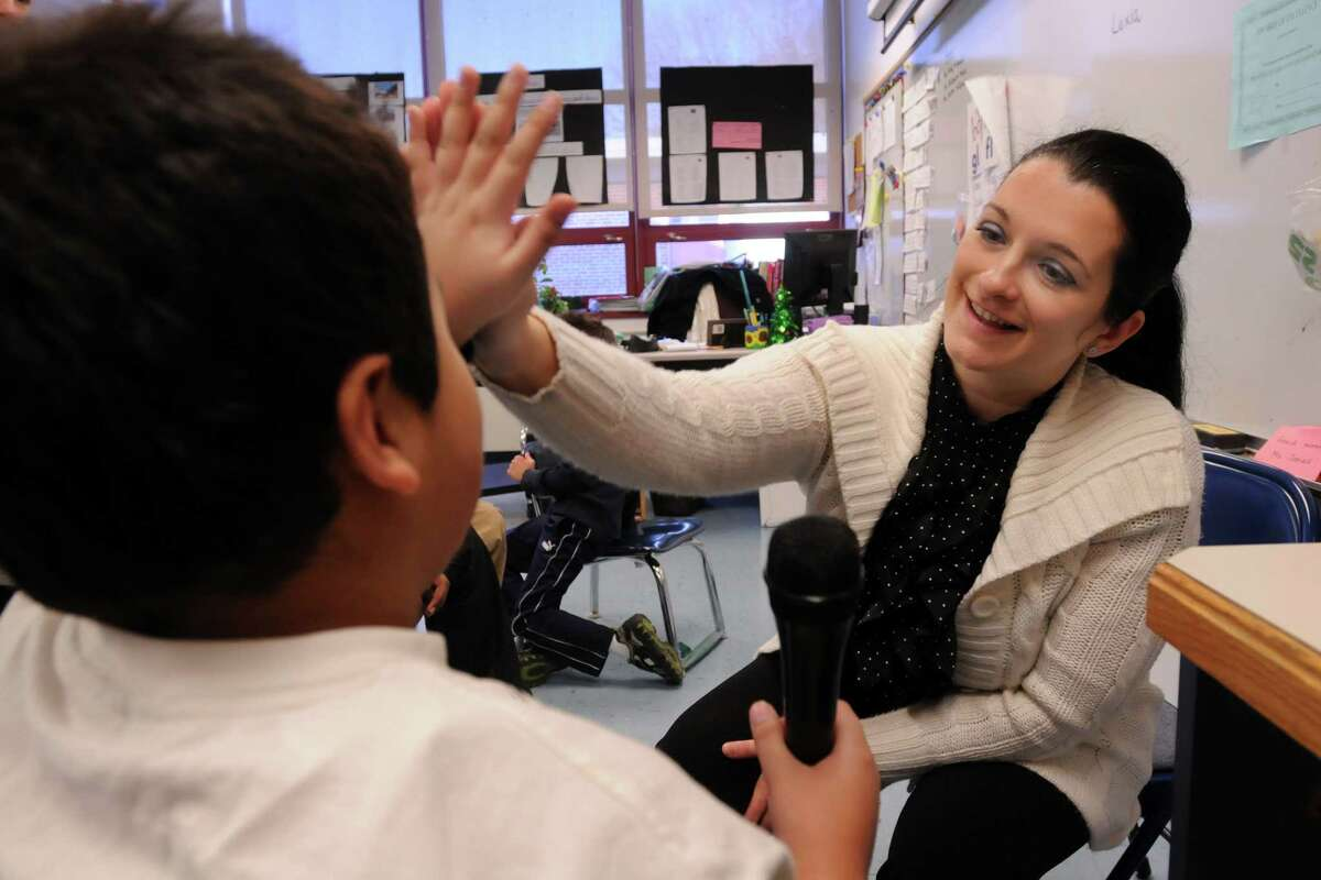 New Haven's Brennan-Rogers School teacher Blanka Jamsek works with her special needs students. She congratulates Kevin Anes left for a good answer to her question. Photo by Mara Lavitt/New Haven Register 12/17/10