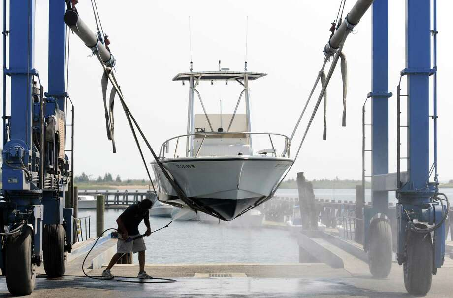 9/2/10 1CL Boat Dave Vitaletti of North Branford washes off his 18' center console power boat after removing it from the water at the Cedar Island Marina in Clinton where he works as a mechanic in preparation for Hurricane Earl. Photo by Mara Lavitt