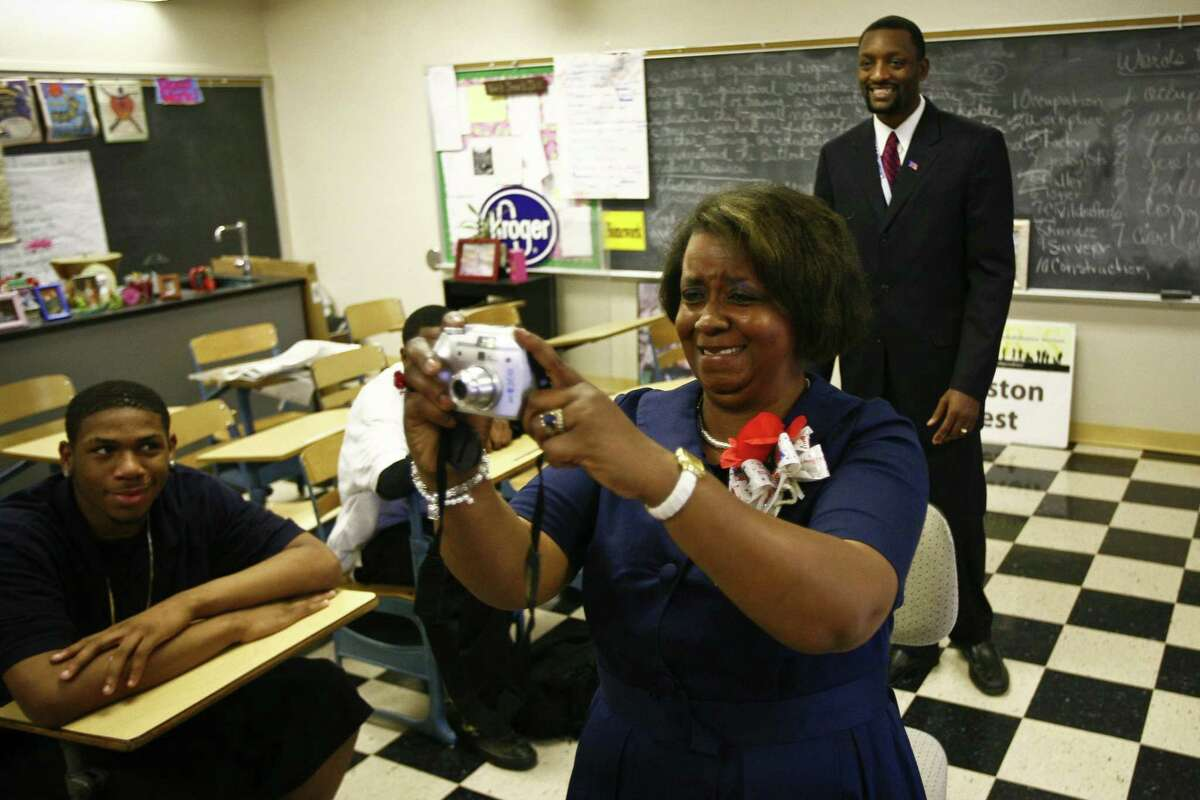 A teacher at Booker T. Washington High School in Houston takes a photo of President Obama raising his hand during the televised inauguration in 2009. Obama, who was the head of the Harvard Law Review, is a good example of someone who used education as a springboard to success.