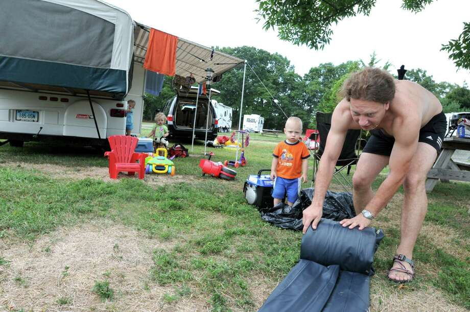 Photography by Peter Hvizdak            ph 2154             #2830 Madison, Connecticut - September 03, 2010:  Patrick Mosur of New Britain, 2, watches his father Piotr Mosur roll up an air mattress as they pack up Friday during an evacuation of the campground at  Hammonasett State Park in Madison because of expected high winds from Hurricane Earl.