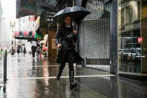 A woman runs down Powell Street during a rainstorm in San Francisco, Calif., on Monday, Jan. 8, 2018.