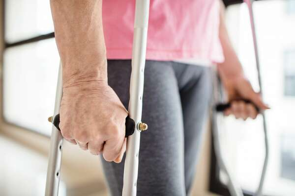 Midsection of senior woman using crutches in hospital. Disabled patient is walking on corridor. She is wearing casual clothing.