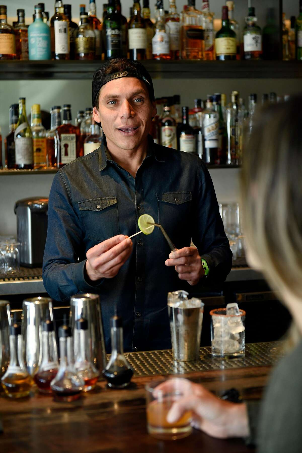 Head bartender Carlos Yturria talks with a customer while making a drink at the White Cap cocktail bar in San Francisco, Calif., on Saturday January 6, 2018.