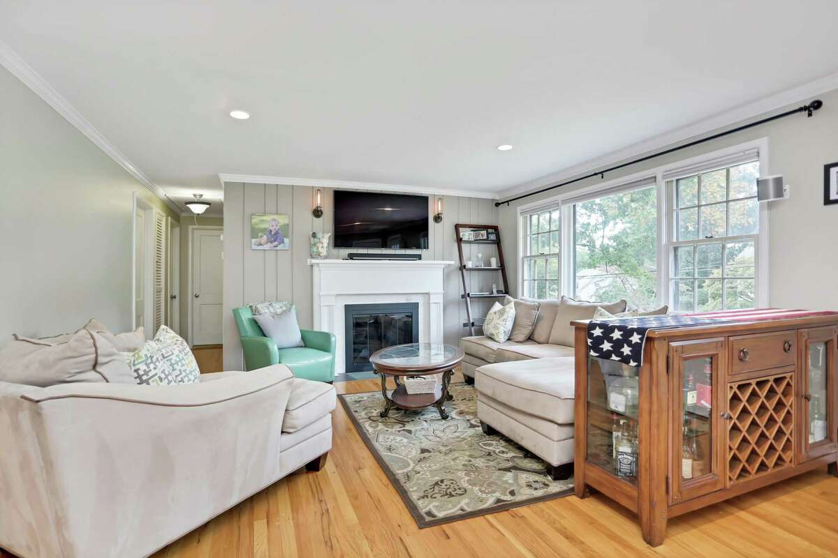 The spacious living room has a fireplace and a large picture window flanked by double-hung windows.