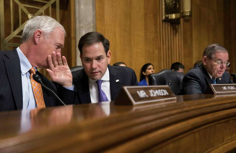 Sen. Marco Rubio, R-Fla., center, confers with Sen. Ron Johnson, R-Wisc., left. Rubio's website indicated that sanctions may be imposed against the Venezuelan oil company PDVSA.  NEXT: See the world's largest oil refineries. Photo: J. Scott Applewhite, Associated Press / Copyright 2018 The Associated Press. All rights reserved.