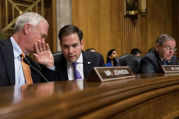 Sen. Marco Rubio, R-Fla., center, confers with Sen. Ron Johnson, R-Wisc., left, as Sen. Bob Menendez, D-N.J., far right, speaks as the Senate Foreign Relations Subcommittee on the Western Hemisphere examines attacks on American diplomats in Havana, on Capitol Hill in Washington, Tuesday, Jan. 9, 2018. (AP Photo/J. Scott Applewhite)
