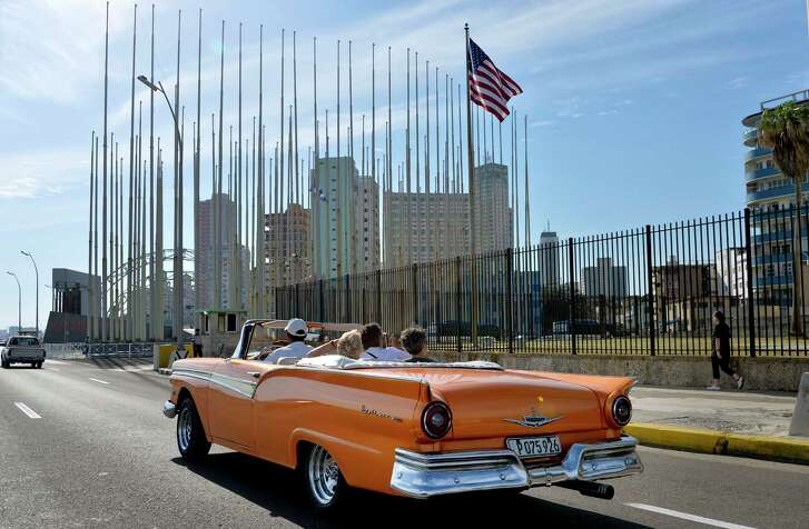An old car passes in front of the U.S Embassy in Havana, Cuba, on March 17, 2016, prior to a visit by U.S. President Barack Obama.