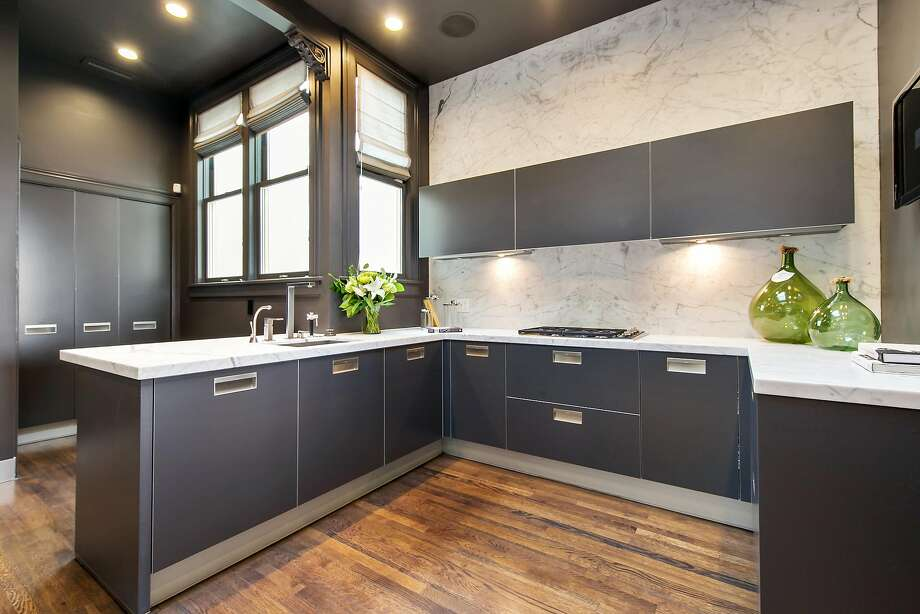 This sleek kitchen on the top level boasts marble counters and custom cabinetry.  Photo: Open Homes Photography