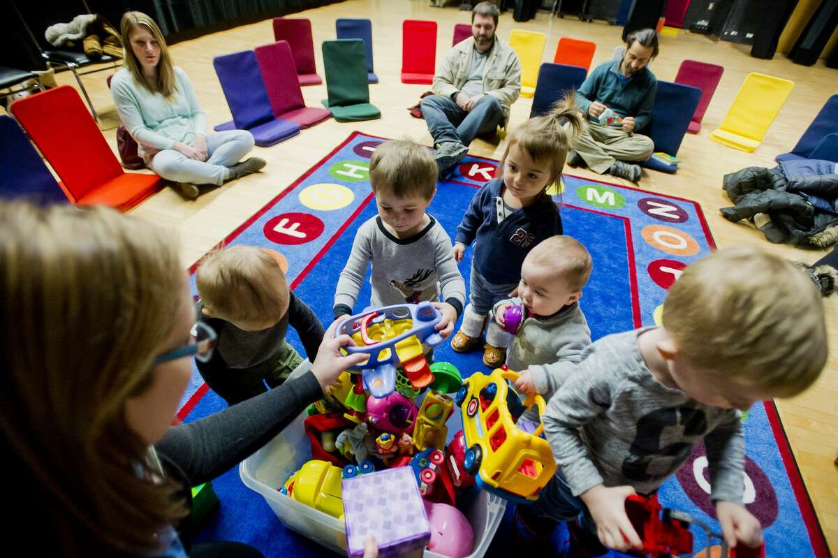 Associate Librarian Deanna Schroden brings out a bucket of toys for a group of children to play with during Toddler Time on Tuesday, Jan. 9, 2018 at the Grace A. Dow Memorial Library. (Katy Kildee/kkildee@mdn.net)