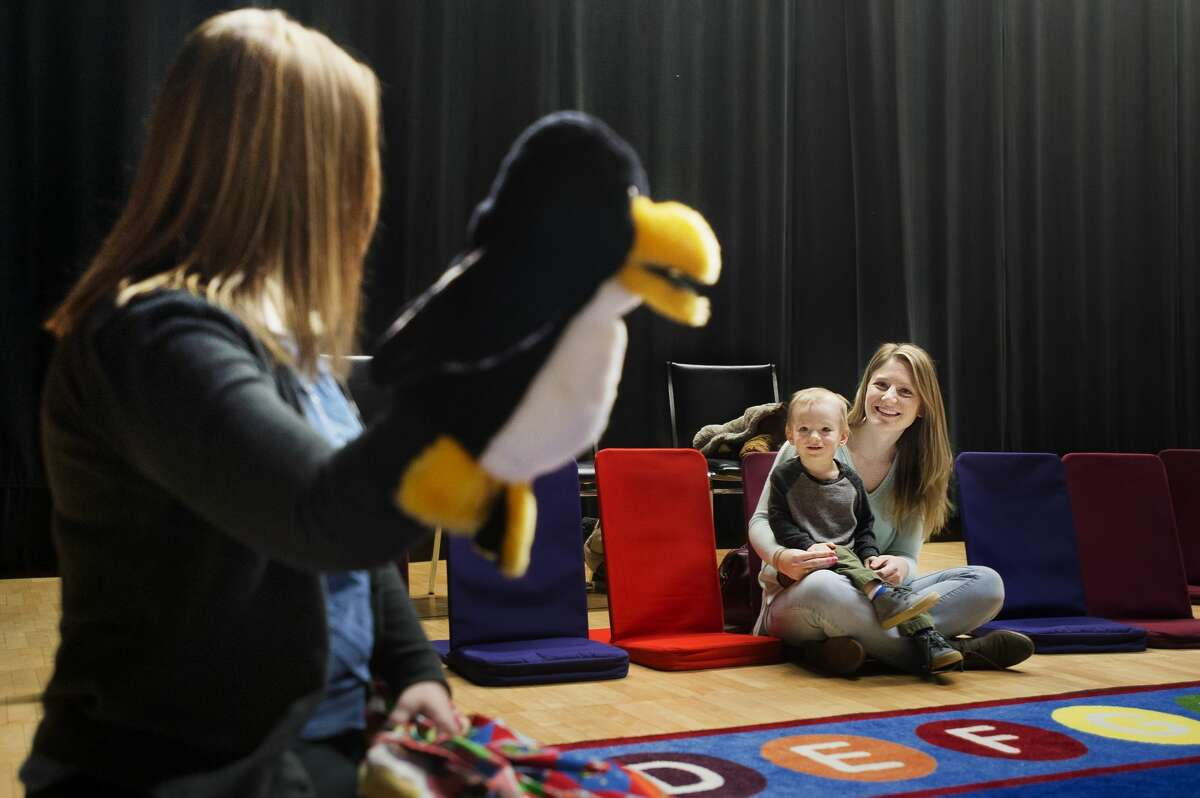 Jess Gable sits with Rex Donner, 1, as they sing along to