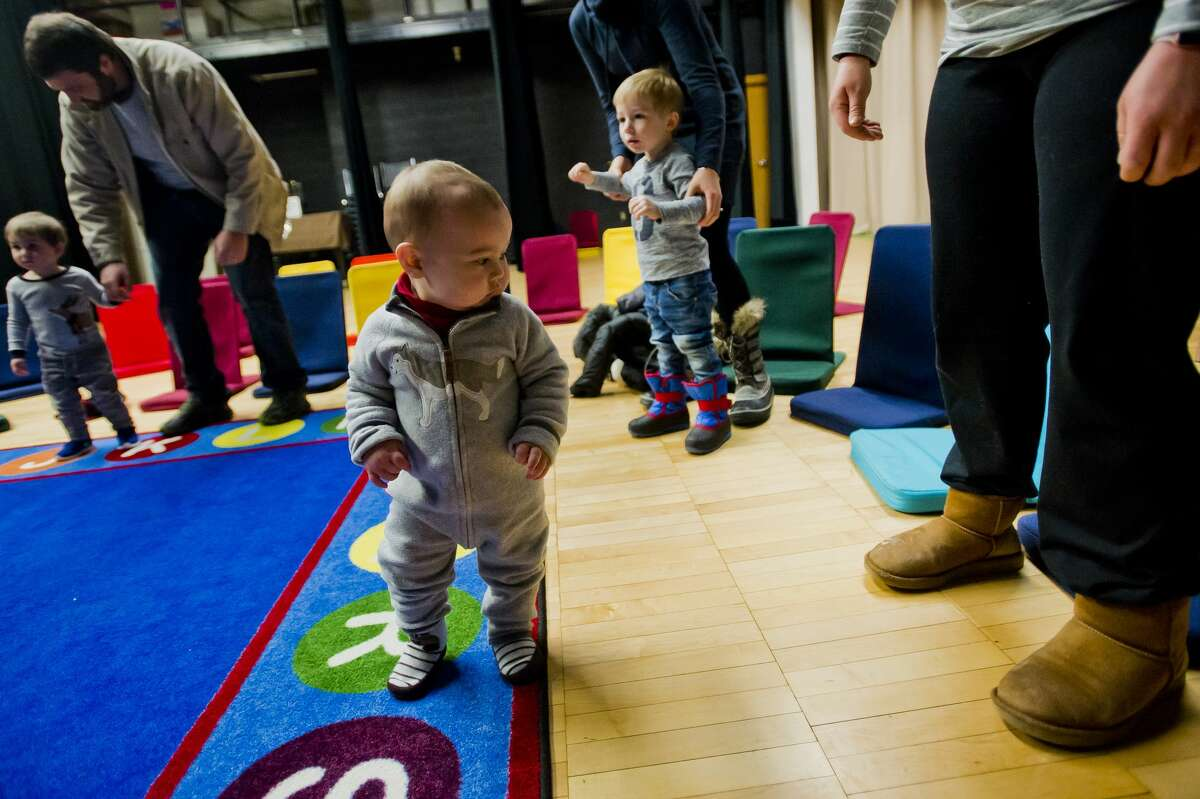 Ethan Evans, 14 months, watches his mom's feet while she dances during Toddler Time on Tuesday, Jan. 9, 2018 at the Grace A. Dow Memorial Library. (Katy Kildee/kkildee@mdn.net)