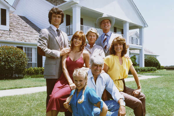A promotional still from the American television series 'Dallas' shows members of the Ewing family as they pose in front of their television home, the Southfork Ranch, Dallas, Texas, 1979. Back row, from left, Patrick Duffy (as Bobby Ewing) (standing), Victoria Principal (as Pamela Barnes Ewing) (in red dress), Barbara Bel Geddes (as Eleanor Southworth 'Miss Ellie' Ewing), and Larry Hagman (as John Ross 'J.R.' Ewing, Jr.). Front row, from left, Charlene Tilton (as Lucy Ewing), Jim Davis (1909 - 1981) (as John Ross 'Jock' Ewing), and Linda Gray (as Sue Ellen Ewing). (Photo by CBS Photo Archive/Getty Images)