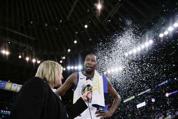 Golden State Warriors player Kevin Durant (35) gets interviewed after defeating the Cleveland Cavaliers in a game at Oracle Arena in Oakland, Calif., on Monday, Dec. 25, 2017.