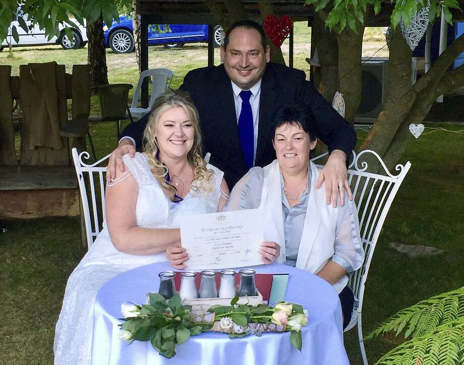 Lainey Carmichael (left) and Roz Kitschke, show their marriage certificate at home near Hobart. Photo: Rodney Croome, Associated Press