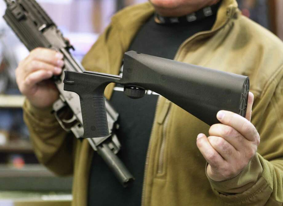 A bump stock device (right), that fits on a semi-automatic rifle to increase the firing speed, making it similar to a fully automatic rifle, is shown next to a AK-47 semi-automatic rifle. Gov. Dannel P. Malloy wants to ban bump stocks and other devices that convert a semi-automatic assault rifle into a machine gun. Photo: George Frey / Getty Images / 2017 Getty Images