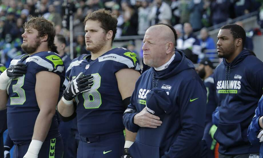 Seattle Seahawks assistant head coach and offensive line coach Tom Cable, second from right, stands with players during the singing of the national anthem before an NFL football game against the Arizona Cardinals, Sunday, Dec. 31, 2017, in Seattle. (AP Photo/Elaine Thompson) Photo: Elaine Thompson/AP
