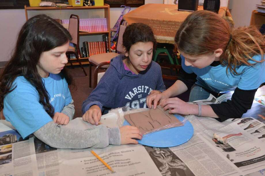 Ryan Lapatine and Alexis Rozen help Chloe Kiev with tracing her hand print in clay during an art project at Beth Israel of Westport/Norwalk Chabad, with the Circle of Friends on Sunday, Jan. 8, in Norwalk. Every month, high-schoolers volunteer to be buddies with children, teenagers and young adults with special needs through Circle of Friends, a program meant to provide social interaction. Photo: Alex Von Kleydorff / Hearst Connecticut Media / Norwalk Hour